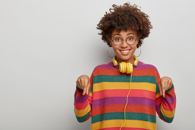Una bella donna etnica punta il dito indice verso il basso, condivide una bella offerta, si sente felice, indossa occhiali e maglione, isolato su sfondo bianco.
