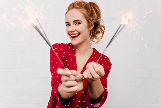 Bella donna europea che celebra le vacanze invernali con le luci del bengala. piacevole ragazza caucasica in pigiama rosso che tiene le stelle filanti e sorridente.