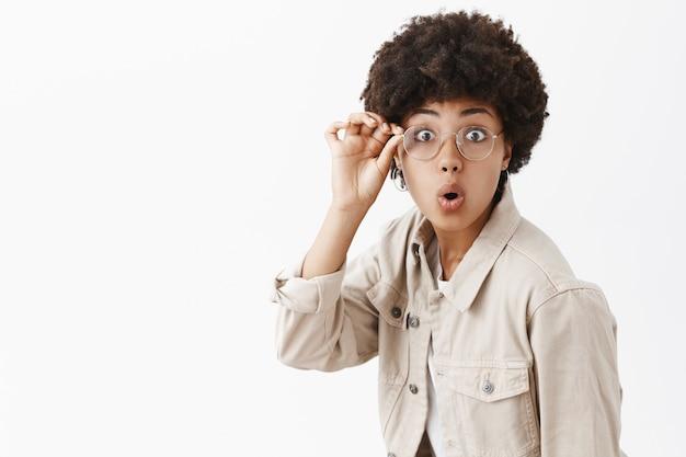 メガネとベージュのシャツを着た見栄えのよいアフリカ系アメリカ人のオタク。アイウェアの縁に触れ、唇を折りたたみ、驚いて見つめ、灰色の壁越しに興味を持っている