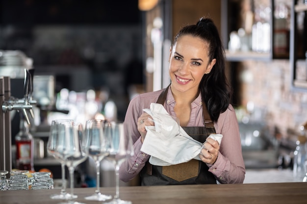 잘 생긴 여성 바텐더는 직장에서 안경을 청소합니다.