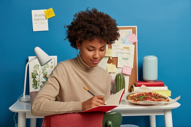 Good looking female has afro haircut takes notes in notepad, writes down own ideas, sits on chair near white desktop with necessary things for work. studying, education concept