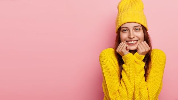잘 생긴 여성 모델은 양손으로 턱을 잡고 세련된 노란색 모자와 스웨터를 입은 카메라에 부드럽게 미소를 짓고 분홍색 벽 위에 모델을 만듭니다.