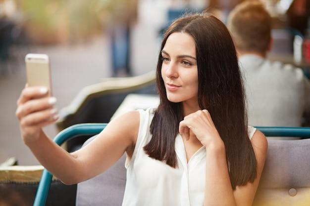格好良い女性モデルは、スマートフォンのカメラでポーズをとって、自撮りを作り、一人で、または恋人と一緒に屋外のカフェテリアで余暇を過ごします。