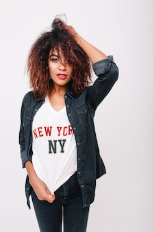 Симпатичная девушка-модель с коричневой кожей играет с темными вьющимися волосами и смотрит с интересом. внутреннее фото чувственно позирующей стройной девушки-мулатки в джинсовом наряде.