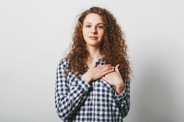 Good looking female model with curly bushy hair keeps hand on chest