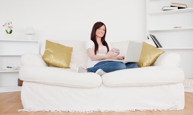 ソファに座って見栄えの良い女性は、インターネットで支払いをするつもりです