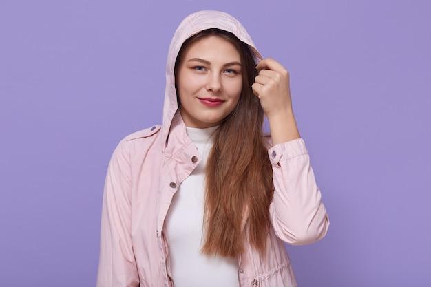 薄紫色の背景に穏やかな笑顔で立っている頭飾りに触れ、フード付きの淡いピンクのジャケットを着て美しい目を持つ格好良い女性。