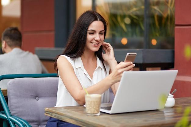 楽しい笑顔で格好良い女性、長い黒髪、スマートフォンを持って、親友からのメッセージを受け取ります