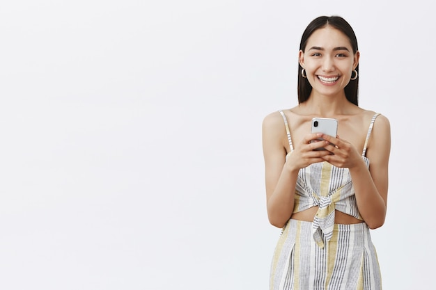 ほくろが唇の下にあり、スマートフォンをじっと見つめながら嬉しそうに笑い、新しいアプリをチェックしている、格好良い優しくて幸せな黒髪の女性。