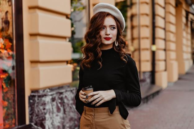 Bella signora francese con una tazza di caffè guardandosi intorno. ragazza riccia pensierosa in camicetta nera che cammina per strada.