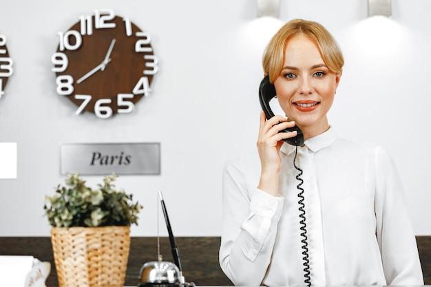 Красивая дружелюбная женщина в приемной отеля разговаривает по телефону крупным планом