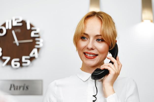 잘 생긴 친절한 여자 호텔 접수가 전화로 이야기를 닫습니다.