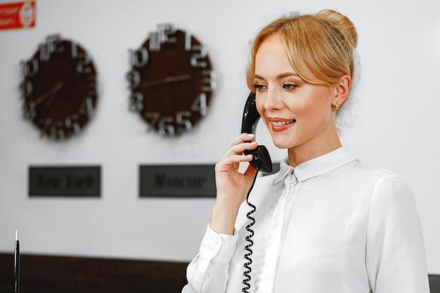 Красивая дружелюбная женщина в приемной отеля разговаривает по телефону