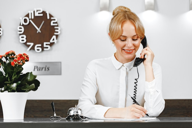 Good-looking friendly woman hotel receptionist talking on the phone close up