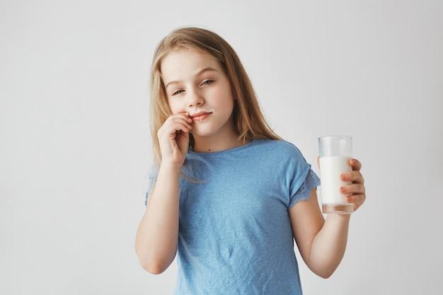 Ragazza bionda divertente di bell'aspetto con gli occhi azzurri che tengono vetro, accarezzando i baffi di latte con la mano che fa espressione subdola del viso.