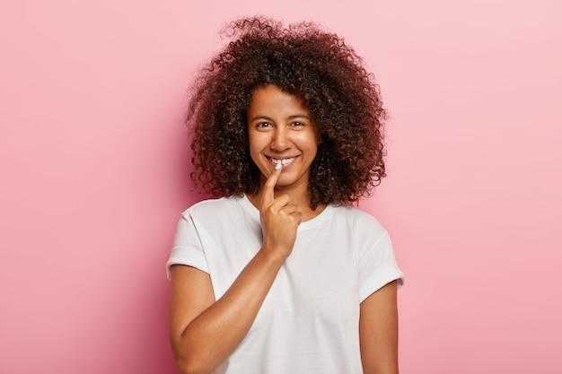 Симпатичная забавная девушка с вьющимися волосами афро, широко улыбается, держит указательный палец на губах, получает интересную идею, обдумывает отличный план, одетая в повседневную одежду, модели на розовой стене