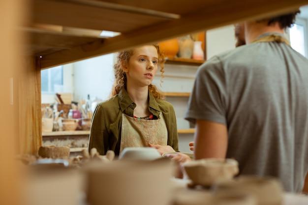 かっこいい生姜の女の子。陶芸工房にいる間、黒髪の相手と話している長髪の生姜少女