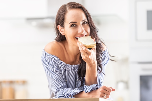 Good-looking girl bites off the slice of bread with a white spread.