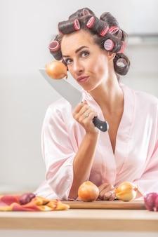 잘 생긴 소녀는 부엌에서 잠옷을 입고 서 있는 동안 손에 든 칼에 양파를 꽂은 채로 카메라를 봅니다.