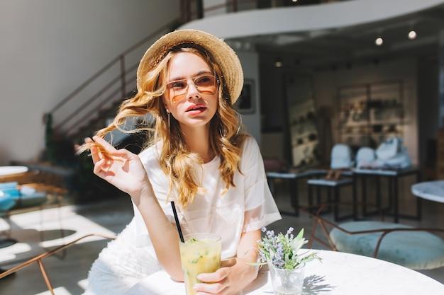 Bella ragazza che gioca con i suoi capelli ricci appoggiati al tavolo con un piccolo vaso di fiori sopra