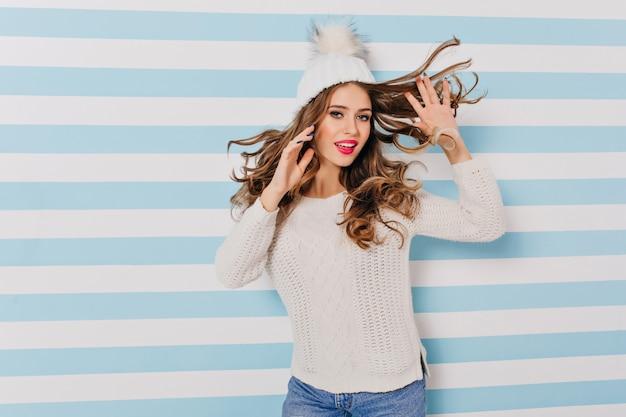 Bella ragazza con i capelli lucidi che balla sulla parete a strisce con l'espressione del viso felice. foto dell'interno del modello femminile dai capelli scuri in cappello lavorato a maglia bianco.