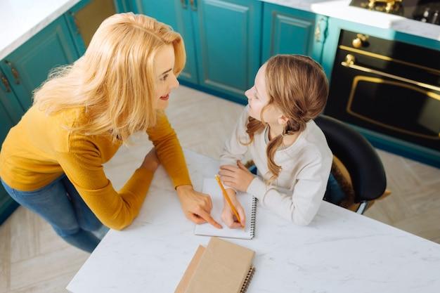 Симпатичная счастливая блондинка стройная мать улыбается и смотрит на свою дочь, сидящую за столом со своим блокнотом