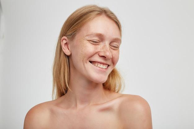Bella donna dai capelli lunghi felice giovane rossa che mostra le sue piacevoli emozioni e sorride allegramente con gli occhi chiusi, in posa contro il muro bianco