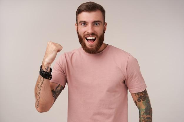 흰색에 서있는 동안 베이지 색 티셔츠와 트렌디 한 액세서리를 입고 유행 헤어 스타일이 넓게 웃고 예 제스처로 주먹을 올리는 좋은 찾고 기쁜 젊은 문신 갈색 머리 남자