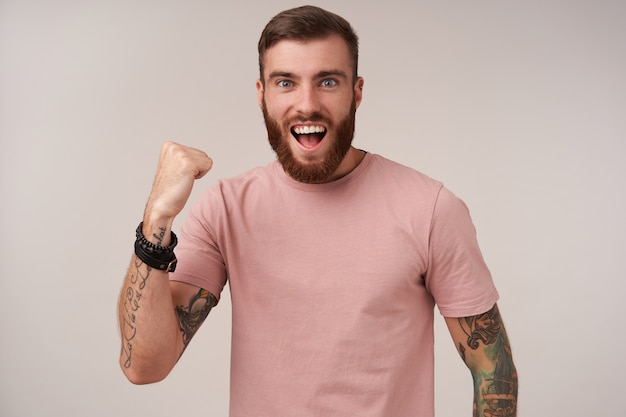 Good looking glad young tattooed brunette man with trendy haircut smiling widely and raising fist in yes gesture, wearing beige t-shirt and trendy accessories while standing on white