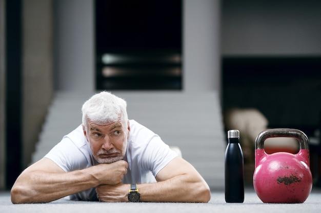 水のボトルと白いシャツを着た格好良い白髪の年配の男性。スポーツとヘルスケアの概念