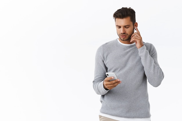 Good-looking guy getting ready leave office, put on wireless headphones, increase volume touch earphone, holding smartphone, looking mobile screen as changing earbuds settings, white wall
