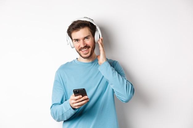 무선 헤드폰으로 음악을 듣고 카메라를 보고 웃고 스마트폰을 사용하고 흰색 배경에 서 있는 잘 생긴 남자.