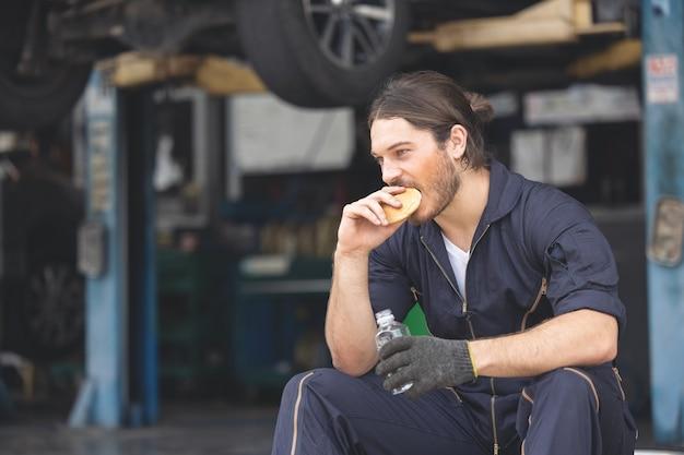 ガレージに座って水休憩を取る格好良い男