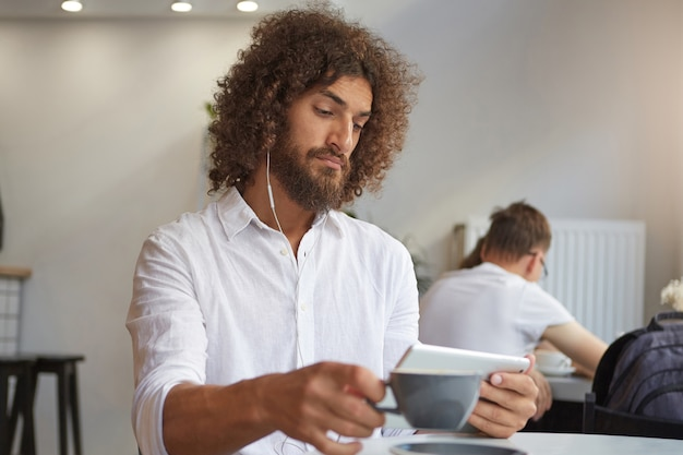 Bello bell'uomo giovane barbuto con capelli ricci castani guardando video sul suo tablet utilizzando gli auricolari mentre beve una tazza di tè, con un aspetto serio e concentrato