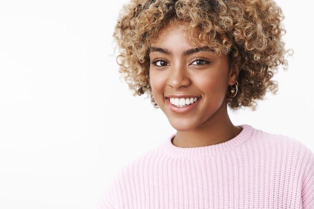 セーターにアフロブロンドのヘアカットをした、かっこいい幸せなアフリカ系アメリカ人の女子学生。カメラを見て満足し、のんびりとした表情で楽しく笑っています。