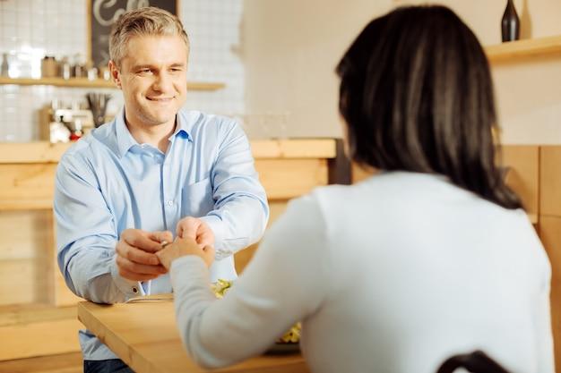 낭만적 인 저녁 식사를하면서 웃고 사랑하는 검은 머리 여자의 손가락에 아름다운 반지를 씌우고 잘 생긴 행복한 금발 남자
