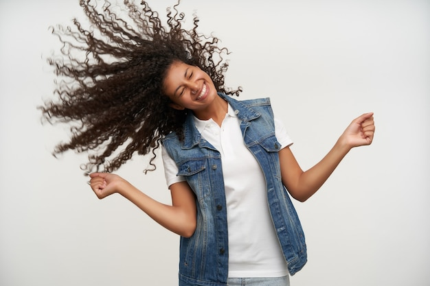 Good looking happy dark skinned female playing with her long curly hair while standing on white in casual clothes, smiling widely and keeping eyes closed