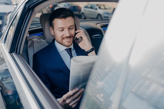 スタイリッシュなフォーマルウェアの格好良い幸せなエグゼクティブマネージャーは、道路交通にとどまりながら、ビジネスパートナーとスマートフォンで話すと同時に車の後部座席で新聞を読みます