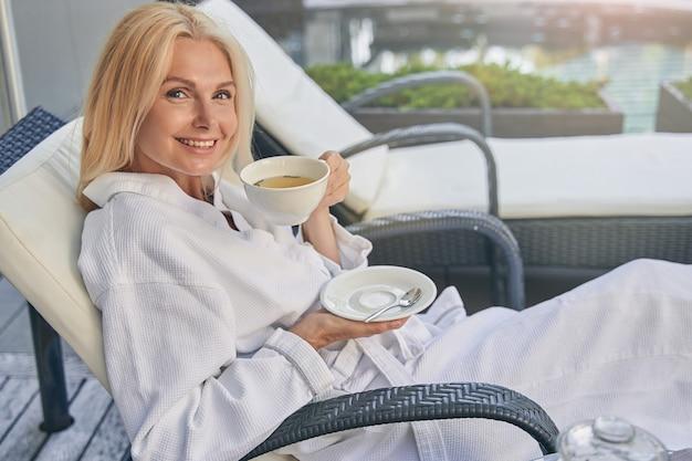 야외에서 차 한잔과 함께 쉬고 흰 목욕 가운을 입고 좋은 찾고 행복한 여성