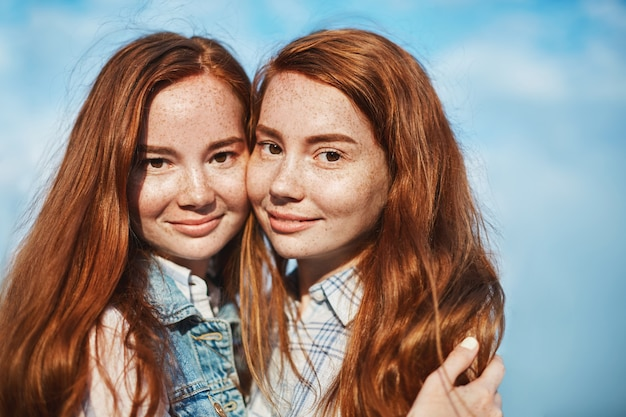Good-looking happy female with red hair and freckles, hugging and smiling, gazing happily, being in close relationship, trusting and loving each other.