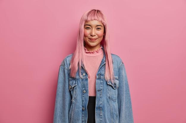 긴 장밋빛 머리카락을 가진 잘 생긴 행복한 소녀는 긍정적 인 태도를 표현하고 긴팔 데님 재킷을 입습니다.