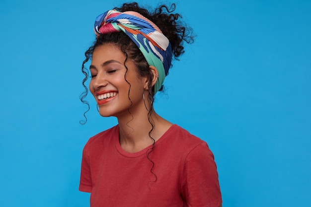 Good looking happy young brunette curly woman with multi-colored headband being in nice mood and miling gladly with closed eyes while standing over blue wall