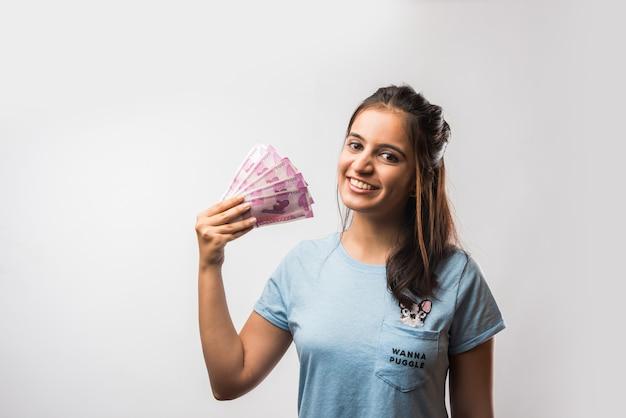 白い背景の上に分離された新しい2000ルピー紙幣で構成されるお金のファンを保持している格好良いインドのアジアの女の子