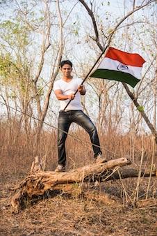 잘 생긴 인도 청년은 공화국 기념일이나 독립 기념일 인사말 카드에 대한 개념적 이미지, 호수 근처 야외에서 인도 삼색기를 들고 손을 흔들거나 달리고 있습니다.
