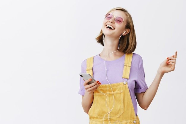 Bella donna allegra che balla con gli occhi chiusi spensierata, tenendo lo smartphone, ascoltando musica in auricolari