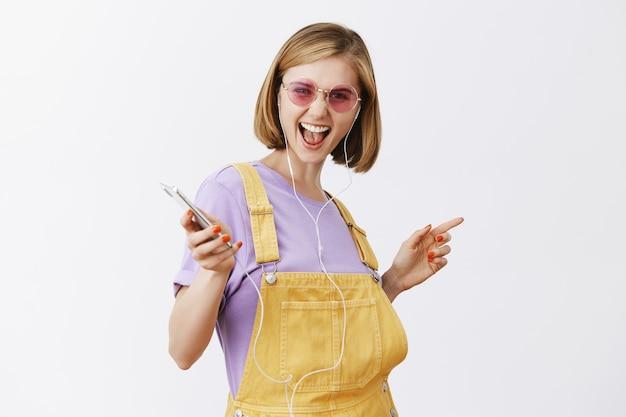 Good-looking joyful woman dancing with closed eyes carefree, holding smartphone, listening music in earphones