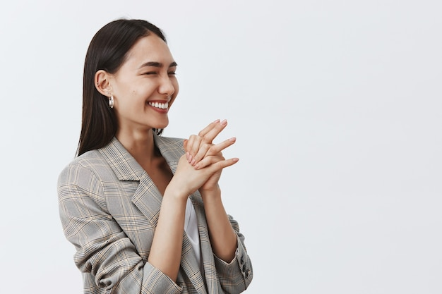 喜びと熱意から笑い、灰色の壁を半分ひっくり返して立って、手を握りしめ、右を向いている、かっこいいうれしそうな女性