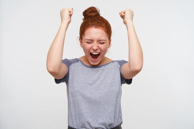 Симпатичная радостная молодая рыжая женщина с непринужденной прической взволнованно поднимает руки и кричит с закрытыми глазами, изолированная над белой стеной в повседневной одежде