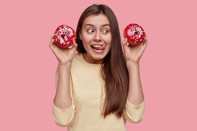Bella signora che si lecca le labbra con la lingua, mangia ciambelle, guarda positivamente da parte