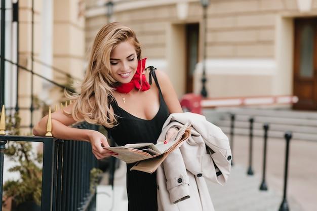 Красивая смеющаяся женщина читает смешную шутку в газете, ожидая друга